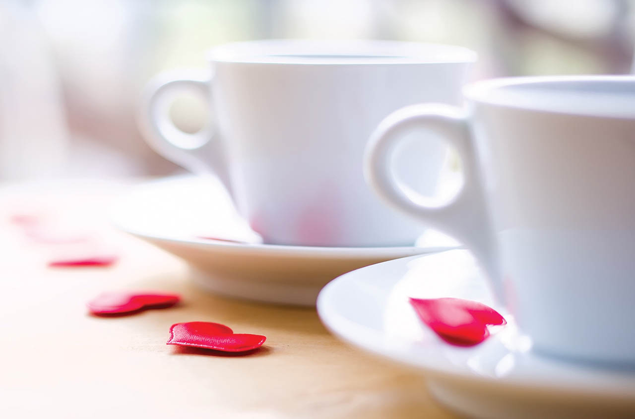 Two white tea cups with red hearts laying on saucer and table