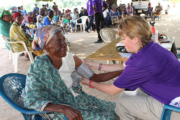 a summer intern takes the blood pressure of an elderly woman during a medical caravan in Ghana, Africa.