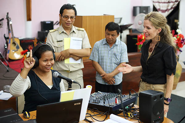 A missionary woman trains members of a church as they prepare to launch a new radio station in Thailand.