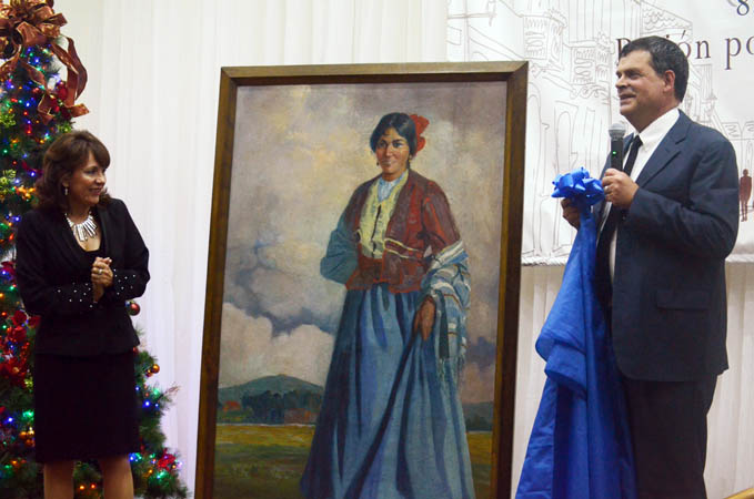 Dan Shedd and Anabella Cabezas present a restored painting to the station by renowned Ecuadorian artist Victor Mideros.