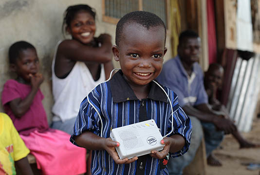 A child holds a SonSet radio in Ghana.