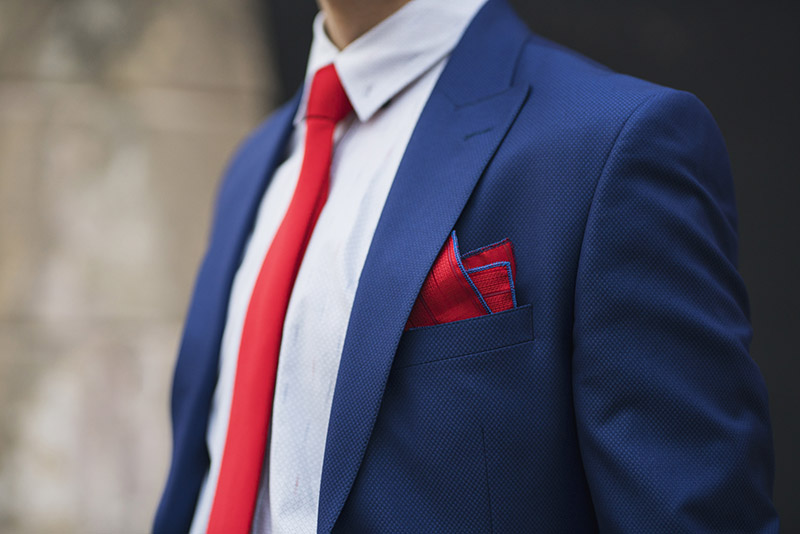Photo of a man wearing a blue suit with red tie