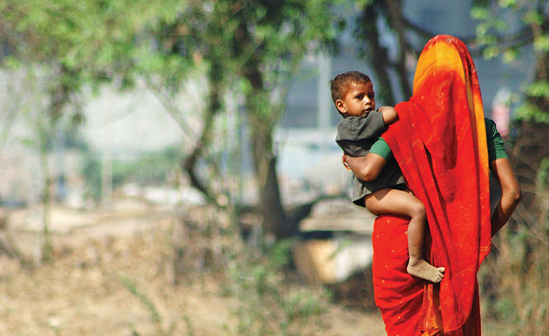 Indian woman wearing a red sari carrying her son