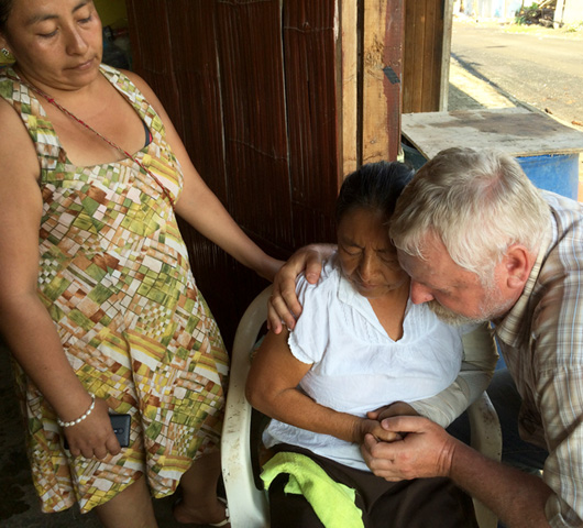 Hermann Schirmacher prays with traumatized victims in Ecuador's earthquake zone.